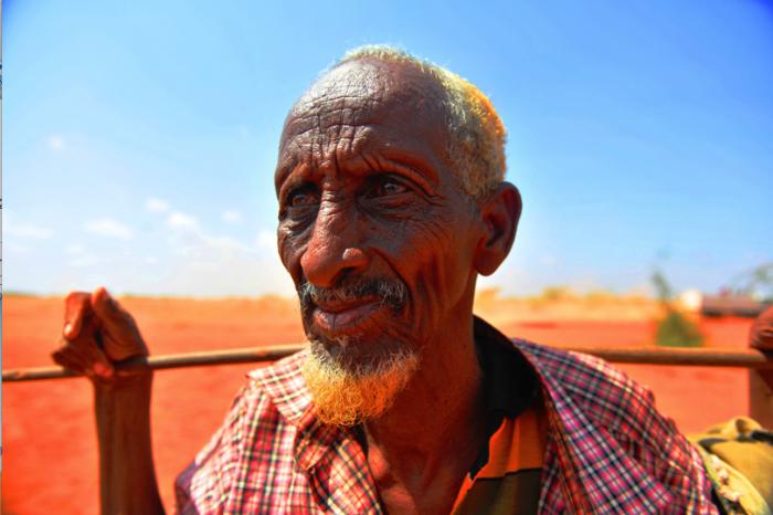写真:ソマリ州で出会ったソマリの男。ラクダ飼いで、貴重な雨でできた水たまりで水を飲ませていた。多くのソマリ人の男性がこのように髪の毛と髭をオレンジ色に染めている。Photo/Kaori Tawara